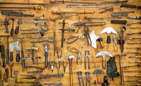 alicates: Diversas herramientas antiguas en la pared en el taller de artesanía en cuero
