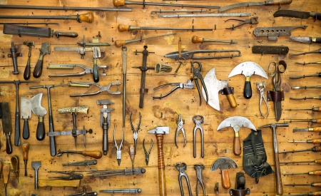 Various old tools on the wall in leather craft workshop photo