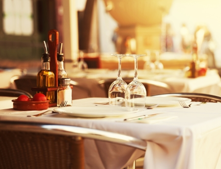 lifestyle dining: Empty outdoor restaurant table at sunset Stock Photo