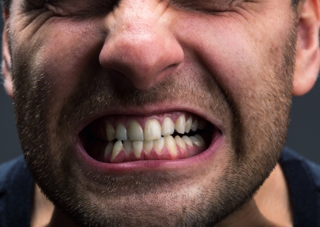 grinding teeth: Closeup of mouth of very stressed man