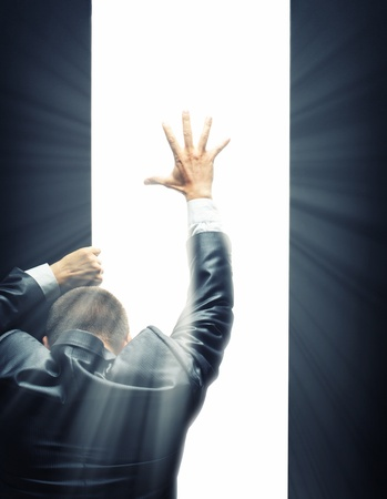 the back gate: Businessman opening some gate and reaching hand to a bright light