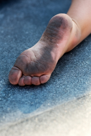 girl soles: Dirty childs foot on the floor Stock Photo