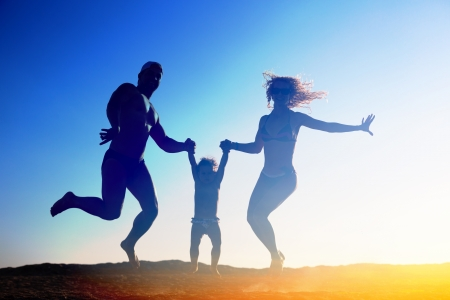 Silhouette of happy family jumping on the beach photo