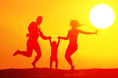 Silhouette of happy family jumping on the beach at sunset photo