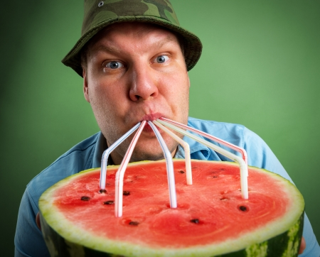 tubules: Bizarre farmer drinking watermelon juice through a tubules Stock Photo