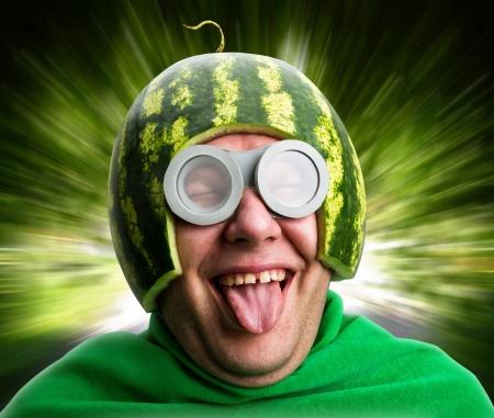 Grappige mens met watermeloen helm en googles ziet eruit als een parasitaire rups Stockfoto