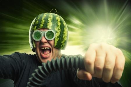 Bizarre man in een helm van een watermeloen snel rijden Stockfoto