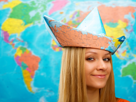 Cute traveler girl in a hat from map photo