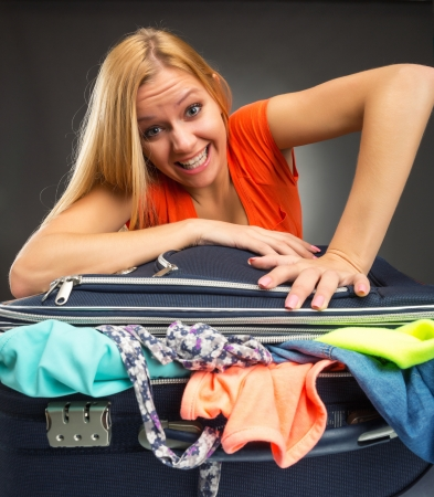 packing suitcase: Young woman struggles to shut a suitcase full of clothing Stock Photo