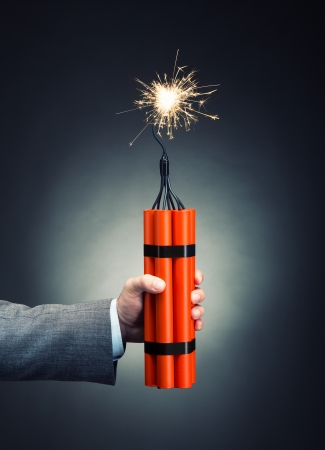 Hand holding dynamite with burning wick Stock Photo