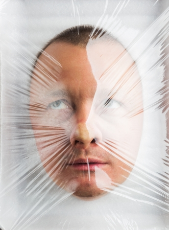 Mans head in Wrapped plastic white food container Stock Photo