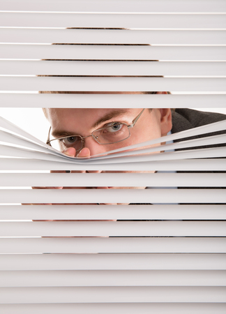 are hidden: A young man looking through window blinds