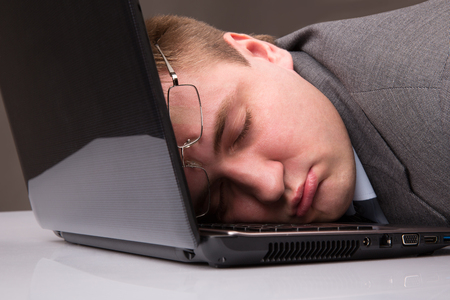 tired worker: Office worker asleep on a laptop keyboard