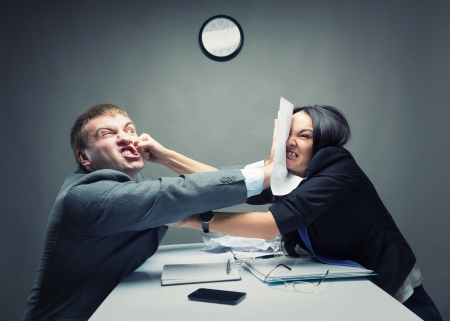 against the clock: Two young caucasian office worker starting to fight Stock Photo