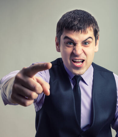 Angry businessman pointing at you. Toned colors photo