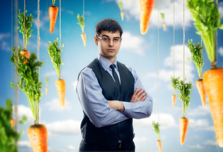 Businessman against blue sky with red carrots  around Stock fotó