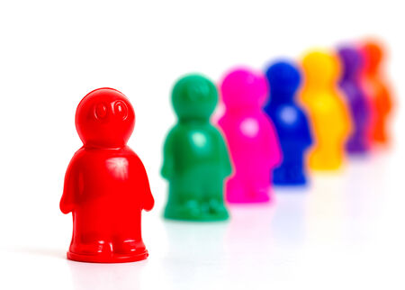 Colorful toy people group in queue on white background photo