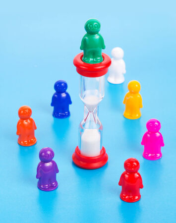 Time is money concept. Colorful toy people standing in a circle around sandclock