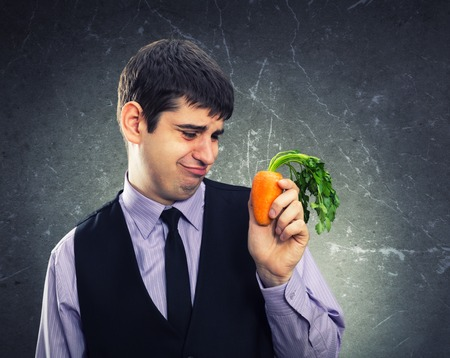 dissapointed: Small carrot in hand of a dissapointed man Stock Photo