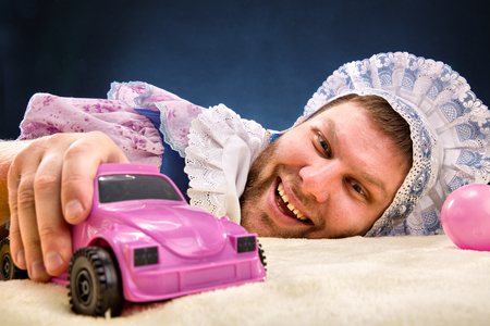 Man weared as baby with toy car photo