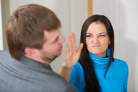 slap: Woman about to slap her partner in living room Stock Photo