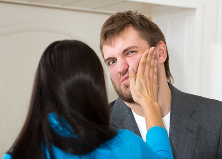 slap: Upset woman slap her partner in living room Stock Photo