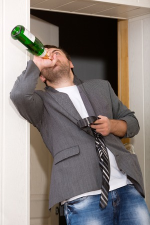 Drunk guy with a bottle of vine indoors photo