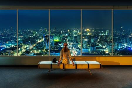 Mirada de la mujer por la ventana en el paisaje urbano de la noche