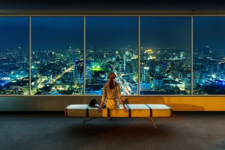 panoramic windows: Woman look out the window at night cityscape