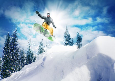 Snowboarder jump against sky and trees photo
