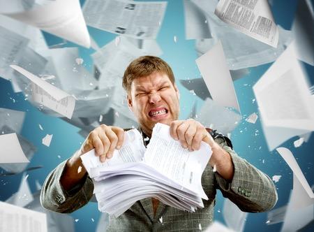 Stressato uomo d'affari strappando risma di carta