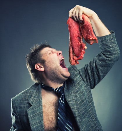 Crazy businessman eating raw meat