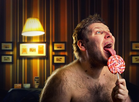 Crazy naked man licking lollipop indoors photo