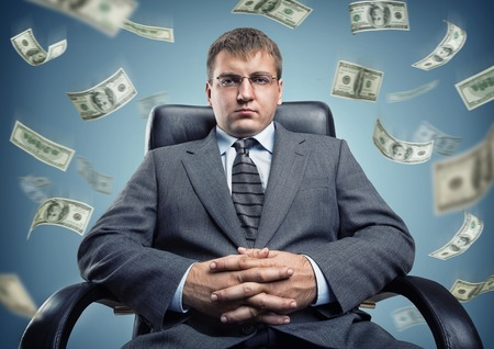 Young businessman in a chair with flying money photo