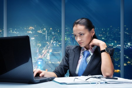 computer problem: Businesswoman working in office against night cityscape Stock Photo