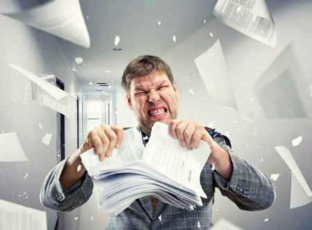 Stressed businessman tearing out stack of paper at office photo