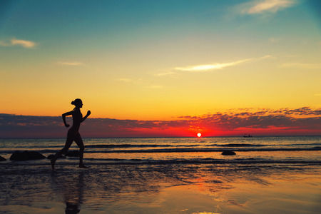 Silhouette of female runing  along the sea coast
