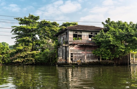 undeveloped: Huts on dirty canal in Thailand