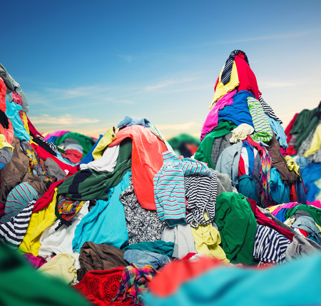Big heap of colorful clothes on sky background