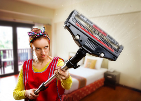 housewife with vacuum cleaner cleaning room photo
