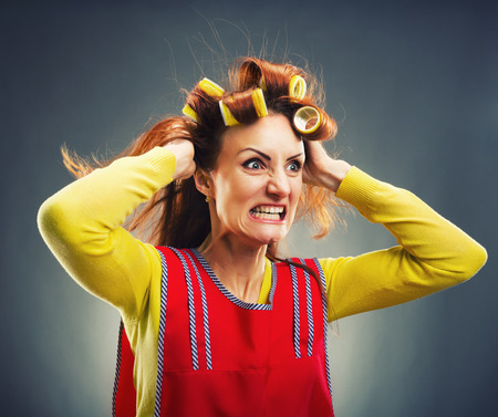 curlers: Crazy housewife with curlers isolated on gray Stock Photo