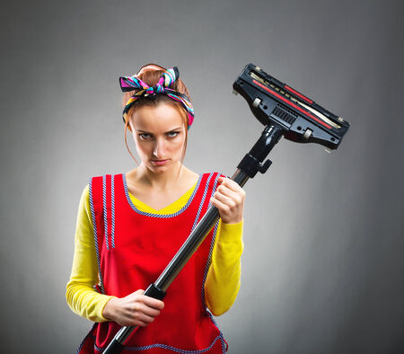 housewife with vacuum cleaner isolated on gray photo