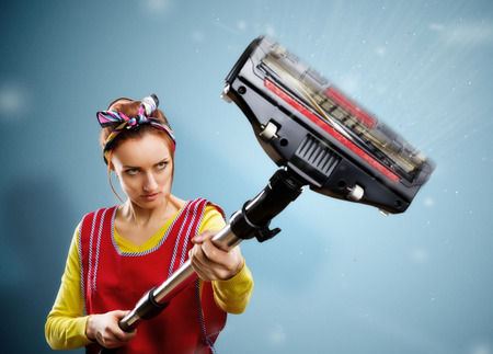 vacuum cleaner: housewife with vacuum cleaner isolated on blue
