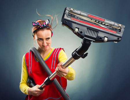 Portrait of housewife with vacuum cleaner isolated on gray photo