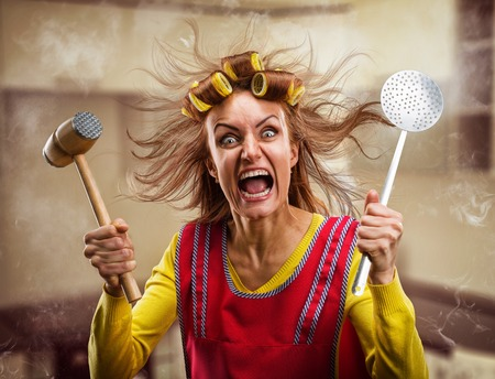 Crazy housewife with hammer on her hand Imagens