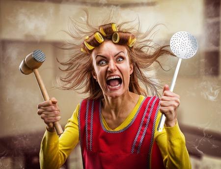 Gekke huisvrouw met een hamer op haar hand