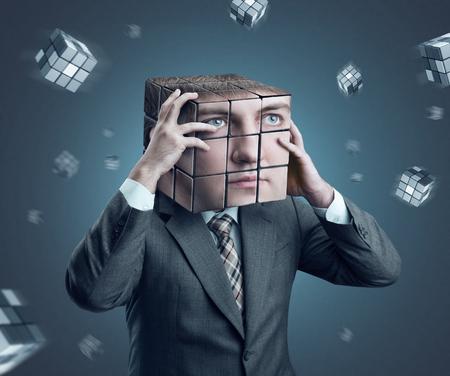 Businessman holding his cube head photo