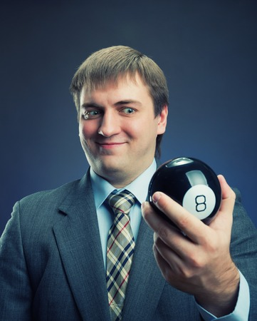 magic ball: Businessman holding magic ball in his hand isolated on gray
