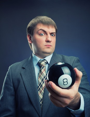 Businessman holding magic ball with number 8 photo
