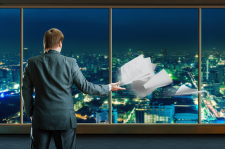 staying: Businessman staying infront window with city view Stock Photo